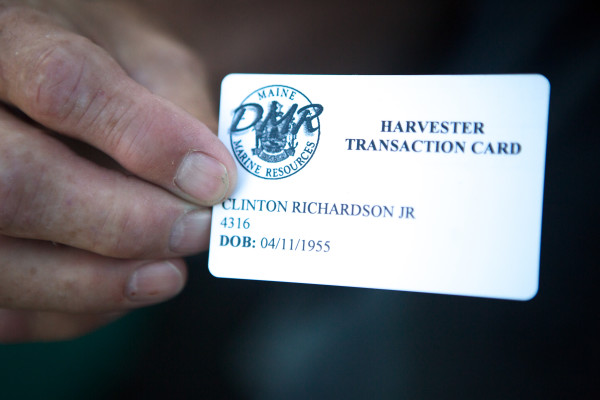 Phippsburg urchin fisherman Clint Richardson shows his new swipe card while selling his catch in Portland. The Maine Department of Marine Resources now requires urchin fishermen and wholesale dealers to use swipe cards to register every transaction for the spiny creatures.
