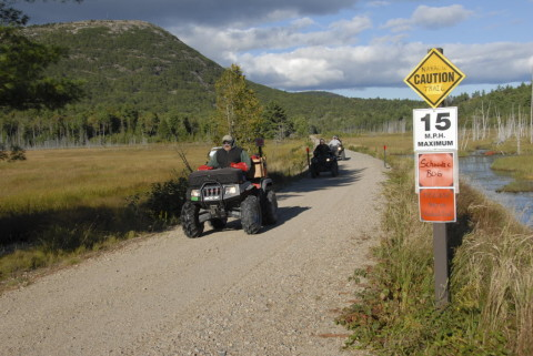 Traveling westbound on the Down East Sunrise Trail between Mile Markers 15 and 16, three ATVs and their riders cross the Schoodic Bog in Sullivan, Sept. 8, 2013.