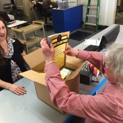 """Ann Davidoff (right) opens a box containing copies of """"Senior Yellow Pages: Local and State Services for Seniors in Greater Bangor"""" at PrintBangor on Central Street. Davidoff is the board president of Gateway Seniors Without Walls, a nonprofit organization serving older residents of the Bangor area. Looking on at left is PrintBangor owner Elena Metzger."""