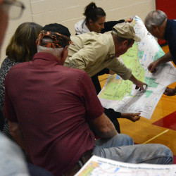 Mount Chase Lodge owner Rick Hill [far right] and others point out locations on a map held by Scarlet McAvoy of Benedicta during during a National Park Service meeting in Stacyville on Thursday.