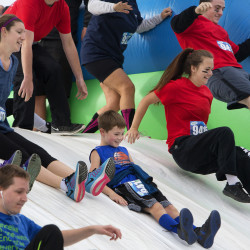 Participants slide down an inflatable slide to start the Insane Inflatable 5K on Saturday at the University of Maine in Orono. The fun run allowed participates to climb, dive, jump and run through different inflatable obstacles.