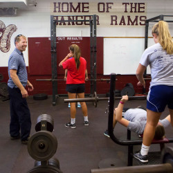 Bangor girl's soccer coach Joe Johnson (left) jokes with his team in the weight room during practice Thursday at the high school. Johnson overcame an underprivileged background to become a successful coach.