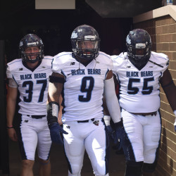 Maine Black Bears place kicker Sean Decloux (37), defensive end Trevor Bates (9), and offensive lineman Bruce Johnson (55) walk onto the field prior to their game against the Boston College Eagles at Alumni Stadium on Sept. 5, 2015.