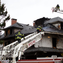 Firefighters work to douse the remaining pockets of flames at the scene of a fatal fire on Noyes Street in Portland on Nov. 1, 2014.