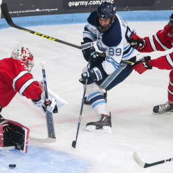 University of Maine's Blaine Byron (center) tries to redirect the puck to goal around Rensselaer Polytechnic Institute's Chase Perry (left) while Tommy Grant puts on the defense during their hockey game on Friday at Alfond Arena in Orono.