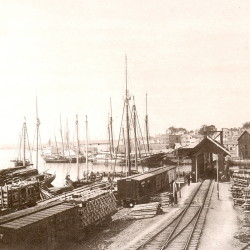 Bangor's harbor was once crowded with sailing ships as this scene at the mouth of the Kenduskeag Stream in the 1880s shows. The railroad drawbridge enabled vessels to sail up the stream to pick up and deliver cargo at warehouses.