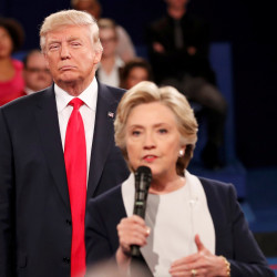 Republican U.S. presidential nominee Donald Trump listens as Democratic nominee Hillary Clinton answers a question from the audience during their presidential town hall debate at Washington University in St. Louis, Missouri, Oct. 9, 2016.