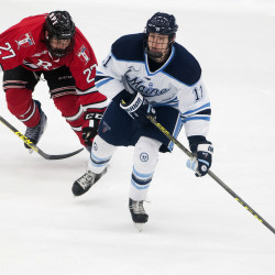 University of Maine's Mitchell Fossier (right) looks to pass past Rensselaer Polytechnic Institute's Jake Wood during their hockey game on Friday at Alfond Arena in Orono.