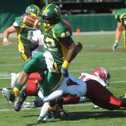 Husson University's Julius Williams (left) tries to break a tackle by Anna Maria College's Lamar Jones in the first quarter of their football game at the Winkin Complex in Bangor in this September 2009 file photo.