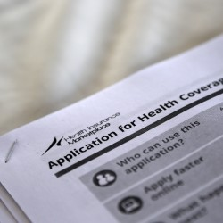 Applications for health coverage are seen at a rally held by supporters of the Affordable Care Act in Jackson, Mississippi, in this October 2013 file photo.