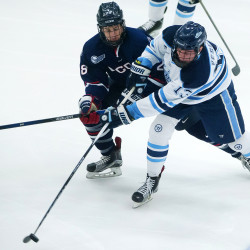 Nolan Vesey (right) of the University of Maine tries to pass around Connecticut's Joey Ferriss during a January 2015 hockey game in Orono. Vesey is hoping to provide leadership playing on a line with two talented freshmen.