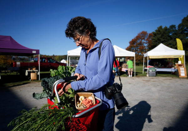 Fine art photographer Lynn Karlin collects vegetables at the farmers market Friday in Belfast.