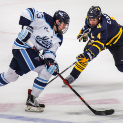 Nolan Vesey of the University of Maine (left) is challenged by Quinnipiac defenseman Connor Clifton during their men's hockey game at Alfond Arena on Friday evening. The Black Bears won 4-3 in overtime.