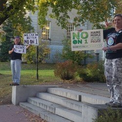 Jeff Walls of Stockton Springs and Tammy Harrison of Hudson hold up signs urging Maine voters to vote no of Question 1 on the Nov. 8 election ballot. While not opposed to legalizing marijuana for recreational use, they said that the proposed legislation would lead to onerous compliance requirements that could force small farmers out of business and adversely affect access to medicine for medical marijuana patients.