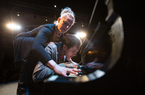 Danielle Erin Rhodes reaches over Jason Cohen to play a duet on the piano at Penobscot Theatre Company while practicing for their show &quotMurder For Two,&quot opening Oct. 21.