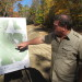 Dana Mosher, outgoing executive director of Camp CaPella, points to details on a map that show the camp's expansion plans on Wednesday in Dedham. Mosher said the expansion will include increased parking, two cabins, a small tenting area and a network of nature trails.