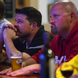 Matthew Silva (center) and Josh Silva (right) watch the last presidential debate at Kosta's Restaurant & Bar in Brewer on Wednesday.
