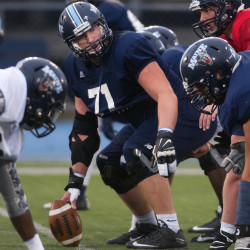 University of Maine's Max Andrews (center) looks to his teammates after calling out the formation during practice on Tuesday at Alfond Stadium in Orono. Andrews, who played at John Bapst, is making his mark at UMaine despite being moved from tight end to center.
