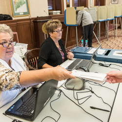 "Irene MacDougall (left) hands a ballot to a voter as Laurie Gifford sits next to her on Thursday at Lewiston City Hall. MacDougall said accusations that the election is rigged are ""ridiculous."""