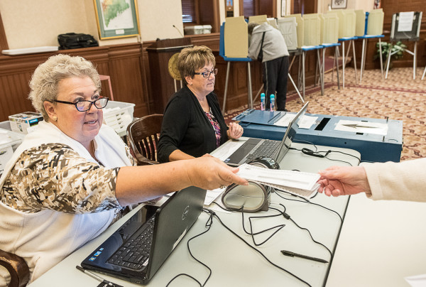 Irene MacDougall (left) hands a ballot to a voter as Laurie Gifford sits next to her on Thursday at Lewiston City Hall. MacDougall said accusations that the election is rigged are &quotridiculous.&quot