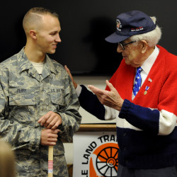 Staff Sgt. Qasey Perry (left), crew chief with the 101st Air Refueling Wing, Maine Air National Guard, receives the 10,000th walking stick from Galen Cole at the Cole Land Transportation Museum in Bangor on Friday morning.