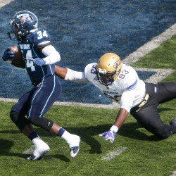 University of Maine's Josh Mack (left) avoids a tackle attempt from James Madison's Andrew Ankrah during their football game at Alfond Stadium in Orono in this September 2016 file photo.