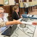 Irene MacDougall (left) hands a ballot to a voter as Laurie Gifford sits next to her on Thursday at Lewiston City Hall.