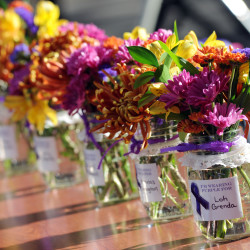Small bouquets in mason jars each with the name of someone who died due to domestic violence in 2013. There were six bouquets.