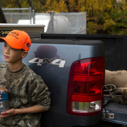 Cade McKenney, 10, leans against his grandfather's truck next to the deer he killed during youth deer day on Saturday at Bob's Kozy Korner in Orrington.