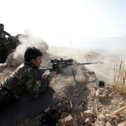 A Kurdish Peshmerga fighter shoots during an operation to attack Islamic State militants in the town of Naweran, near Mosul, Iraq, Oct. 23, 2016.