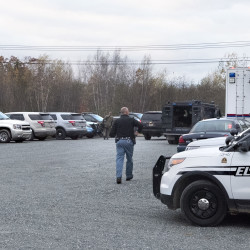 Police are staged in a parking lot on the Bucksport Road in Ellsworth Monday. They are looking for Aaron Wagner, 41, who is suspected of firing a gun at an occupied vehicle Sunday.