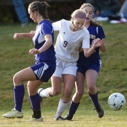 Orono's Brinsley Chasse (center) battles to move the ball through Bucksport's Darian Jellison (left) and Meaghan Goodine during their Class C North girls soccer championship game at Orono in this November 2015 file photo.