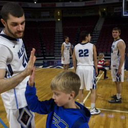University of Maine's Ilker Er (left) gives a young fan a high five during the basketball media day and kids clinic on Tuesday at the Cross Insurance Center in Bangor.