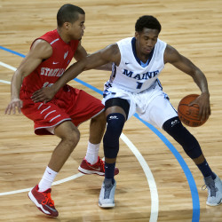 University of Maine's Aaron Calixte (right) spins around Stony Brook University's Carson Puriefoy during their basketball game at the Cross Insurance Center in Bangor in this January 2015 file photo.