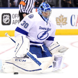 Ben Bishop of Tampa Bay makes a save during Tuesday night's NHL game at Toronto. The former University of Maine goaltender had his top front two teeth knocked out by a shot that hit him in the mask, but he stayed in the game and registered a 7-3 victory.