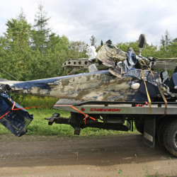 The crumpled remains of a plane that crashed in a man-made pond in Houlton on Aug. 27, 2015, are removed from the site on the back of a flatbed trailer.