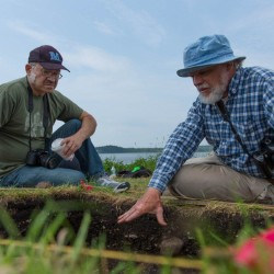 University of Maine Associate Professor of Anthropology Brian Robinson (right) and Donald Soctomah, historic preservation officer for the Passamaquoddy Tribe, examine one of the dig sites at Long Point in Machiasport that Robinson and his crew excavated in July 2013.