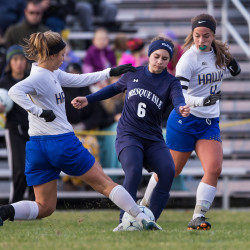 Presque Isle's Charlotte Carrier (center) fends off two Hermon players during their playoff game at Hermon High School on Monday evening.