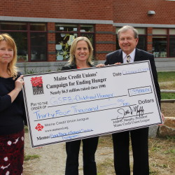 "(l-r) Dr. Beverly McMillan, Principal of Ocean Avenue Elementary School in Portland (site of the first school backpack program in Maine), Kristen Miale, President of Good Shepherd Food Bank, and John Murphy, President of the Maine Credit Union League.  Murphy presented the first installment of a new three-year, $100,000 commitment announced by the Maine Credit Unions' Campaign for Ending Hunger to expand and support the school backpack and pantry programs across Maine.  Good Shepherd called this contribution ""an amount that will benefit children in every region of Maine."""