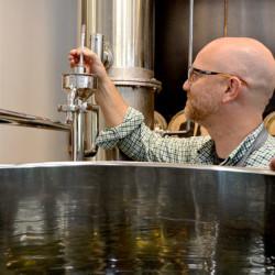 Split Rock Distilling co-founder Matt Page checks the temperature of the still Monday, Oct. 3.