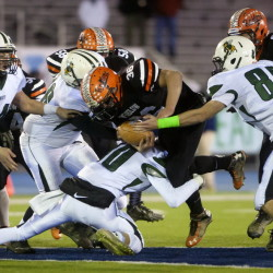 Winslow's Ken Rickard (center) pushes through Leavitt players for yardage during their Class C football state championship game at the University of Maine's Alfond Stadium, Nov. 21, 2014.