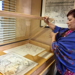 Lise Pelletier, director of the Acadian Archives at the University of Maine at Fort Kent, opens a display case containing original maps from the 1500s on display.