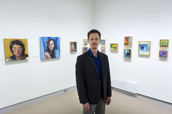 Maine artist Philip Frey poses for a portrait in front of a selection of his artwork on display at the University of Maine Museum of Art in Bangor on Sept. 22.