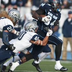 University of Maine's Josh Mack (right) pushes for yards past New Hampshire's Pop Lacey (center) and Casey DeAndrade during their football game Saturday at Alfond Stadium at the University of Maine in Orono.