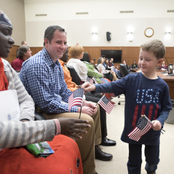 Four-year-old Logan Donald (right) hands out American flags to people before a naturalization ceremony Monday at the Margaret Chase Smith Federal Building in Bangor. Christopher Donald (center), Logan's father, was one of the 23 people from 15 countries who became citizens of the U.S. during the ceremony.