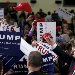 Republican presidential candidate Donald Trump throws an autographed hat back into the crowd at a campaign rally in Cadillac, Michigan, March 4, 2016.