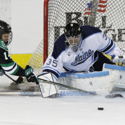 University of Maine's Rob McGovern blocks the goal as University of North Dakota's Austin Poganski, left, tries to make a shot during the first period of their game Saturday, October 10, 2015 at the Cross Insurance Arena in Portland, Maine.