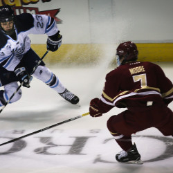 University of Maine's Sam Becker (left) battles for the puck with Boston College's Connor Moore on Friday night at the Cross Insurance Arena in Portland.