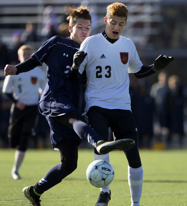 Yarmouth's Eric LaBrie (left) and Winslow's Jackson Morneault battle for the ball during their Class B boys state championship soccer game at Hampden Academy Saturday.