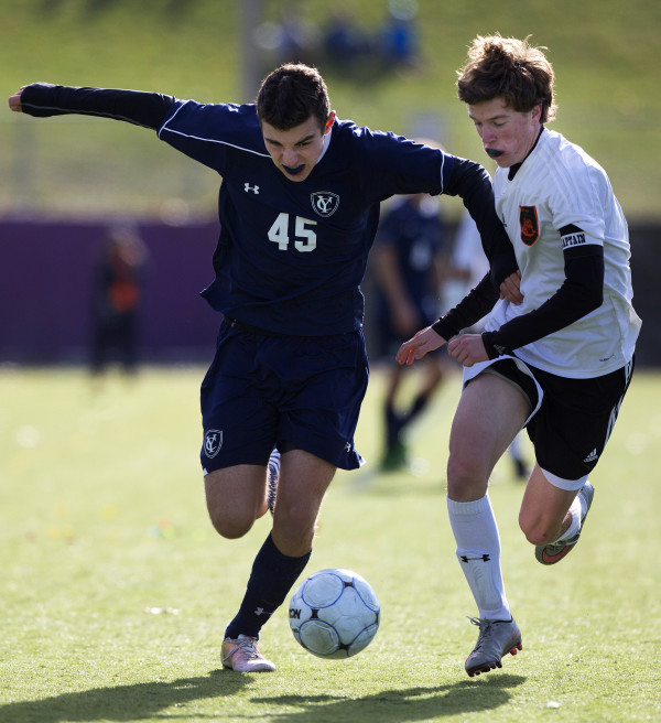 Yarmouth's Gibson Harnett (left) runs hard for a ball against Winslow's Ben Smith during their Class B boys state championship soccer game at Hampden Academy Saturday.